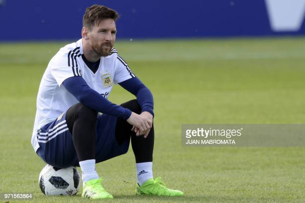 Argentina's forward Lionel Messi looks on as he sits on a ball during a training session of Argentina's national football team at the team's base...