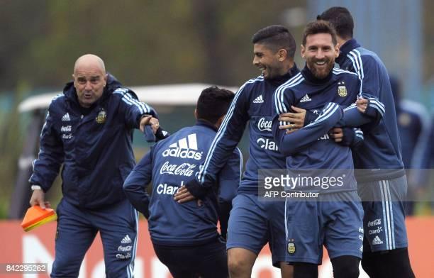 TOPSHOT Argentina's forward Lionel Messi midfielder Ever Banega and midfielder Angel Di Maria joke around during a training session in Ezeiza Buenos...