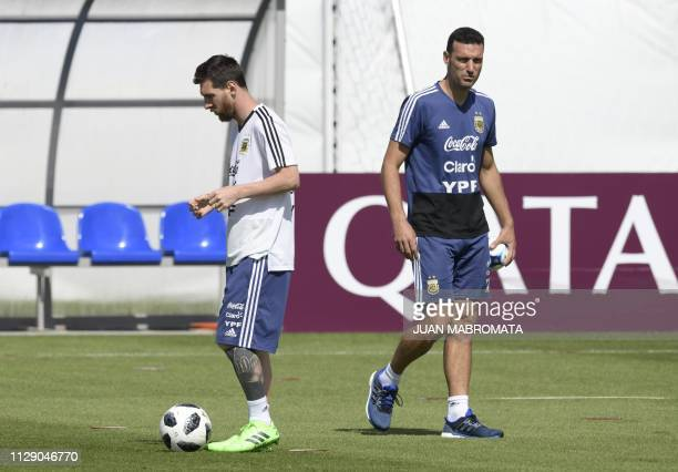 Argentina's forward Lionel Messi passes the ball next to assistant coach Lionel Scaloni during a training session at the team's base camp in...