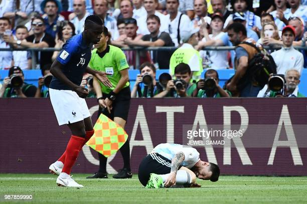 Argentina's forward Lionel Messi reacts following a challenge by France's midfielder Blaise Matuidi during the Russia 2018 World Cup round of 16...