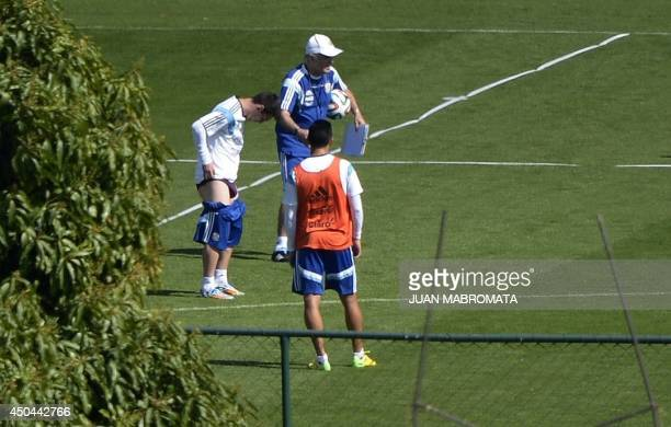 Argentina's forward Lionel Messi rearranges his shorts next to coach Alejandro Sabella and defender Ezequiel Garay during a closed training session...