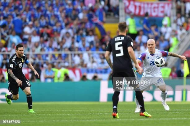 Argentina's forward Lionel Messi runs towards Iceland's midfielder Emil Hallfredsson as he challenges Argentina's midfielder Lucas Biglia during the...