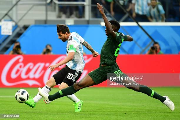 TOPSHOT Argentina's forward Lionel Messi shoots score as he is marked by Nigeria's defender Kenneth Omeruo during the Russia 2018 World Cup Group D...