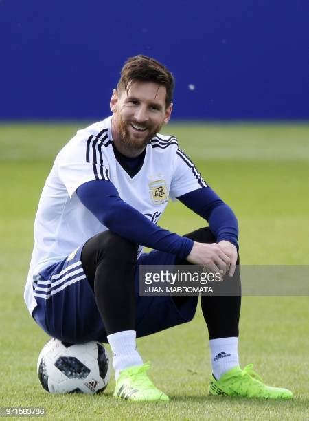 Argentina's forward Lionel Messi smiles as he sits on a ball during a training session of Argentina's national football team at the team's base camp...