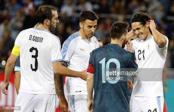 Argentina's forward Lionel Messi talks to Uruguay's forward Edinson Cavani during the friendly football match between Argentina and Uruguay at the...