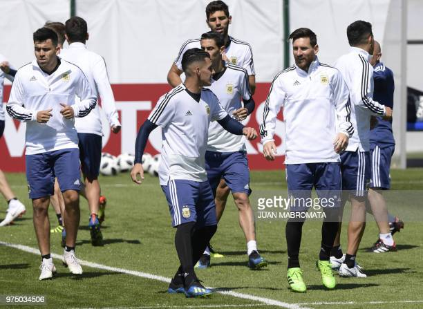 Argentina's forward Lionel Messi talks with midfielder Cristian Pavon as they warm up during a training session at the team's base camp in Bronnitsy...