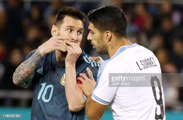 TOPSHOT Argentina's forward Lionel Messi talks with Uruguay's forward Luis Suarez during the friendly football match between Argentina and Uruguay at...