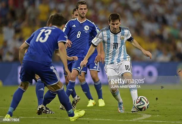 Argentina's forward Lionel Messi vies BosniaHercegovina's midfielder Miralem Pjanic and BosniaHercegovina's midfielder Mensur Mujdza during the Group...