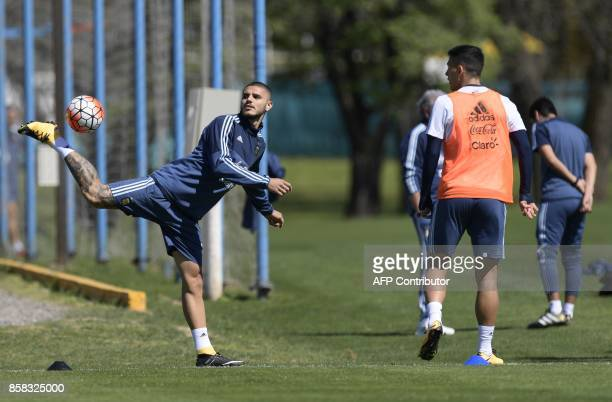Argentina's forward Mauro Icardi passes the ball next to midfielder Leandro Paredes during a training session in Ezeiza Buenos Aires on October 6...
