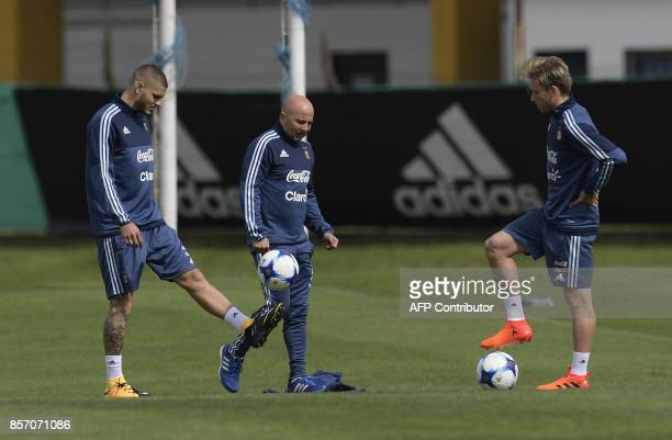 Argentina's forward Mauro Icardi plays with a ball next to coach Jorge Sampaoli and midfielder Lucas Biglia during a training session in Ezeiza...
