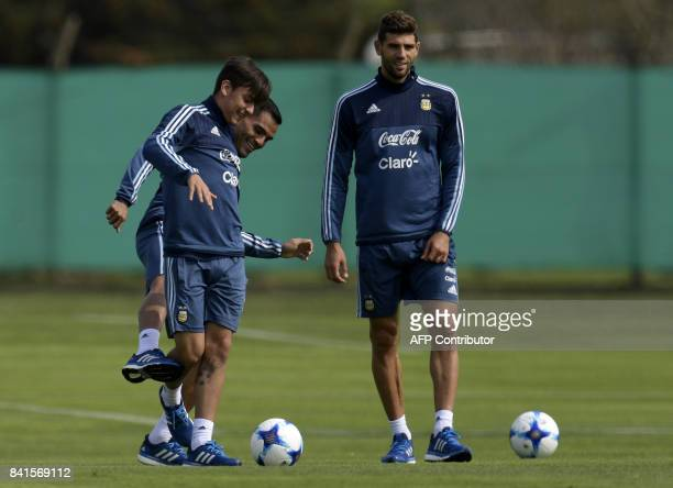 Argentina's forward Paulo Dybala and defender Gabriel Mercado joke next to defender Federico Fazio during a training session in Ezeiza Buenos Aires...