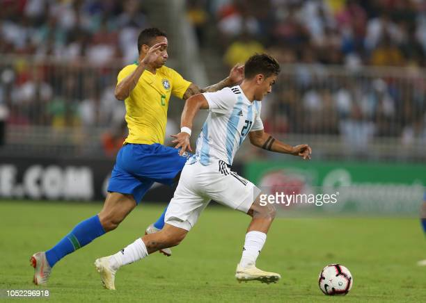Argentina's forward Paulo Dybala drives the ball past Brazil's defender Danilo during the friendly football match Brazil vs Argentina at the King...