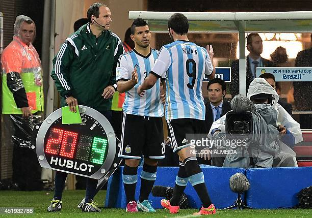Argentina's forward Sergio Aguero shakes hands with Argentina's forward Gonzalo Higuain as he comes onto the pitch to replace him during the...