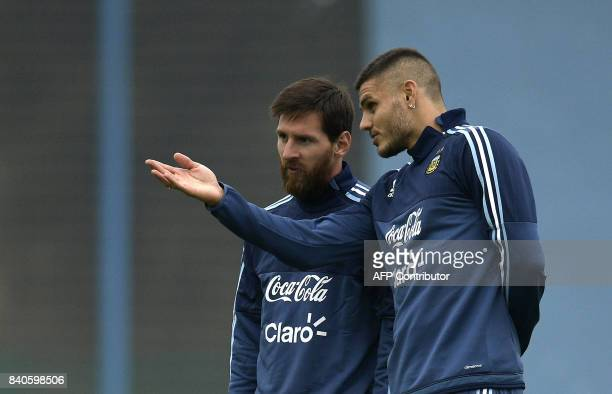 Argentina's forwards Lionel Messi and Mauro Icardi talk during a training session in Ezeiza Buenos Aires on August 29 2017 ahead of their FIFA World...