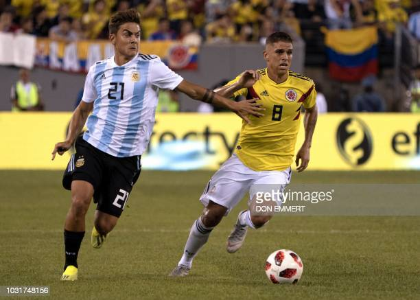 Argentina's foward Paulo Dybala vies for the ball with Colombia's midfielder Gustavo Cuellar during the international friendly match between Colombia...