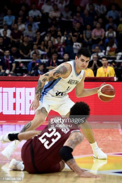 Argentina's Gabriel Deck dribbles the ball as Venezuela's Michael Carrera lies on the court during the Basketball World Cup Group I second round game...