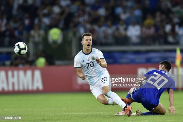 Argentina's Giovani Lo Celso is fouled by Paraguay's Matias Rojas during their Copa America football tournament group match at the Mineirao Stadium...
