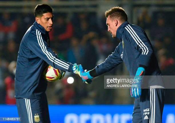 Argentina's goalkeeper Esteban Andrada and Argentina's goalkeeper Franco Armani shake hands as they warm up before the start of the international...