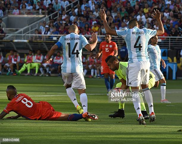 Argentina's goalkeeper Sergio Romero catches the ball next to teammates Javier Mascherano and Gabriel Mercado as Chile's Arturo Vidal lies on the...
