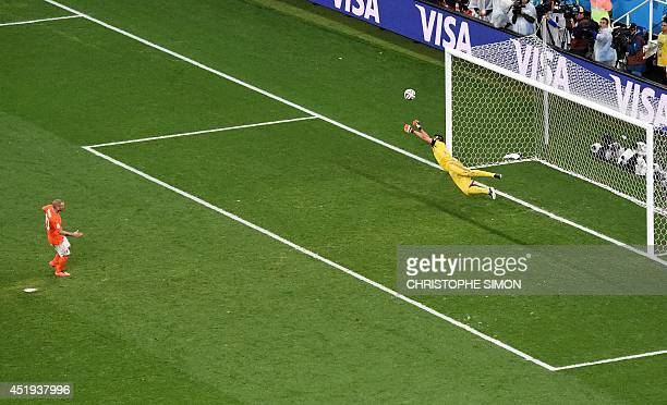 Argentina's goalkeeper Sergio Romero makes a save against Netherlands' midfielder Wesley Sneijder during a penalty shootout of the semifinal football...