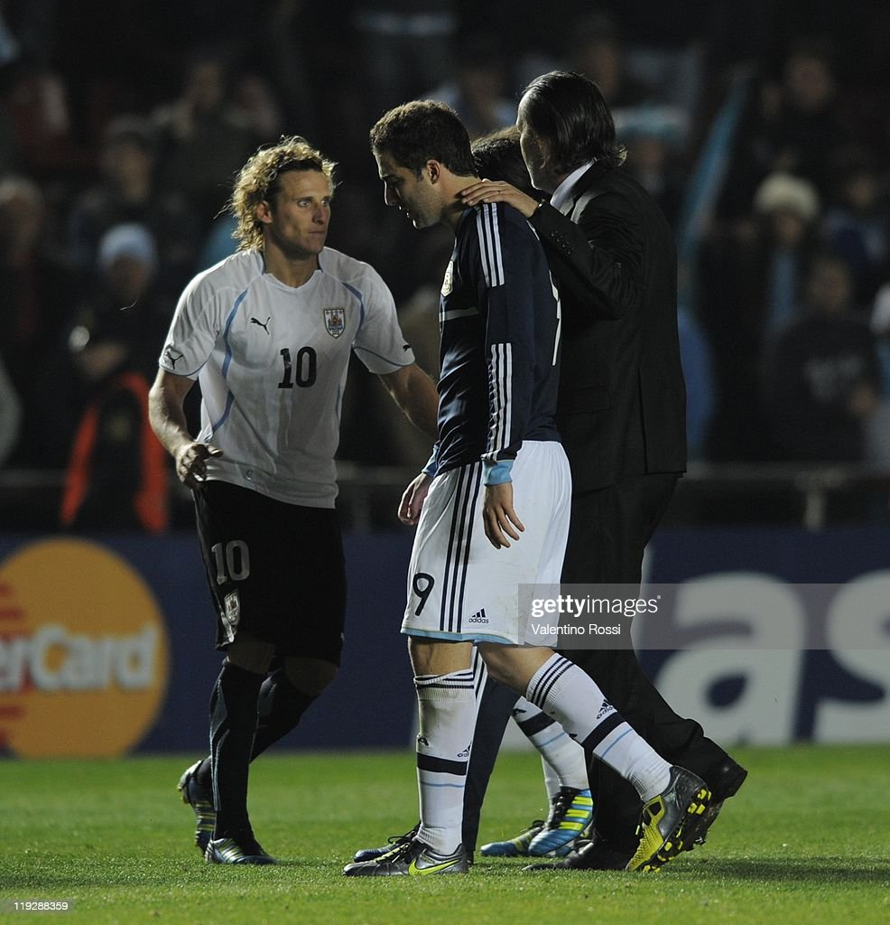 Argentina's Gonzalo Higuain (C) react after missing the penalty serie as Diego Forlan (L) greets during 2011 Copa America soccer match as part of quartes final at Brigadier Estanislao Lopez stadium on July16, 2011 in La Plata, Argentina.