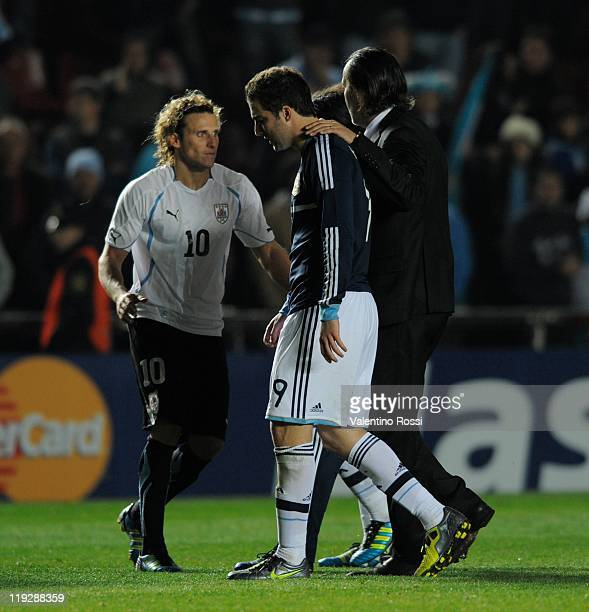 Argentina's Gonzalo Higuain react after missing the penalty serie as Diego Forlan greets during 2011 Copa America soccer match as part of quartes...