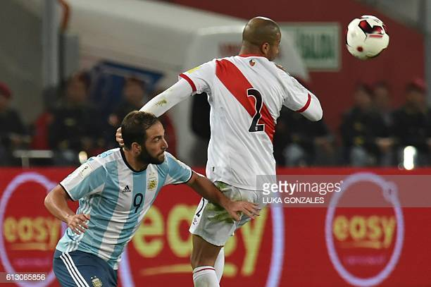 Argentina's Gonzalo Higuain vies for the ball with Peru's Alberto Rodriguez during their Russia 2018 World Cup football qualifier match in Lima on...