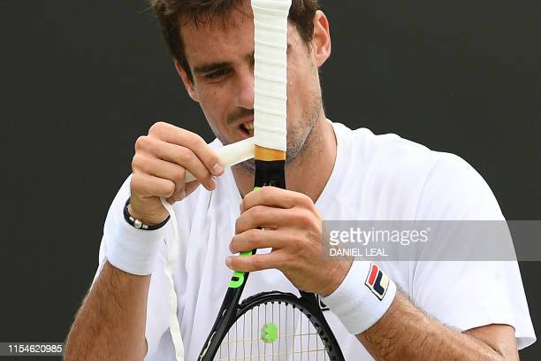 Argentina's Guido Pella applies tape on his racquet during his men's singles fourth round match against Canada's Milos Raonic on the seventh day of...