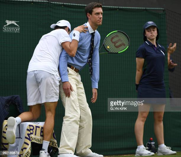 Argentina's Guido Pella crashes into a line judge as he plays against Croatia's Marin Cilic during their men's singles second round match on the...