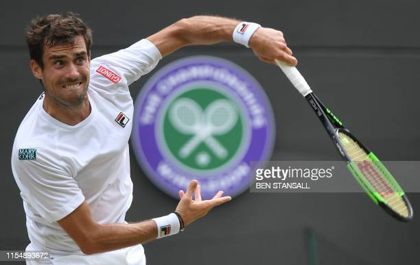 Argentina's Guido Pella serves to Spain's Roberto Bautista Agut during their men's singles quarterfinal match on day nine of the 2019 Wimbledon...