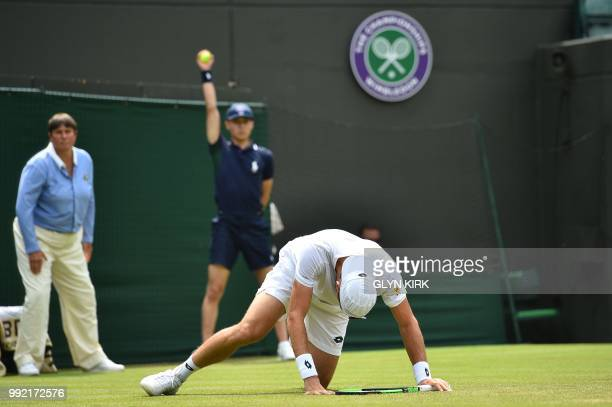 Argentina's Guido Pella slips on the grass as he plays against Croatia's Marin Cilic during their men's singles second round match on the fourth day...