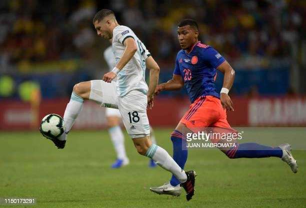 Argentina's Guido Rodriguez controls the ball as Colombia's Roger Martinez follows him during their Copa America football tournament group match at...