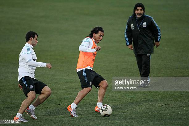 Argentina's head coach Diego Maradona watches on as Carlos Tevez keeps the ball away from Javier Mascherano during a team training session on June...