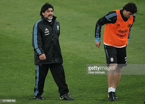 Argentina's head coach Diego Maradona watches on as Diego Milito limps off the field after hurting his ankle during a team training session on June...