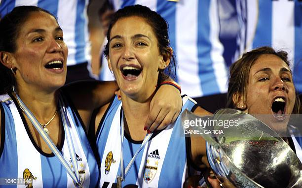 Argentina's hockey players Soledad Garcia Luciana Aymar and midfielder Ana Rodriguez Perez sing as they hold the trophy after defeating Netherlands...