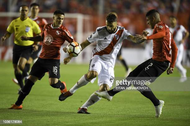 Argentina's Independiente defender Fabricio Bustos and defender Alan Franco vie for the ball with Argentina's River Plate forward Lucas Pratto during...