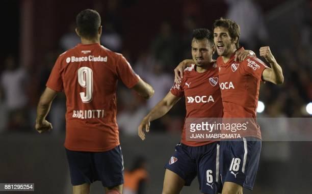 Argentina's Independiente defender Juan Sanchez Mino defender Fabricio Bustos and forward Emmanuel Gigliotti celebrate after defeating 31 to...