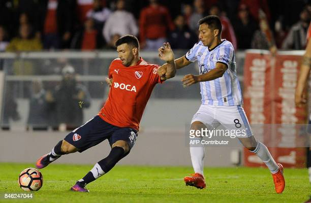 Argentina's Independiente forward Emanuel Gigliotti vies for the ball with Argentina's Atletico Tucuman midfielder Guillermo Acosta during the Copa...