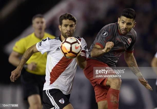 Argentina's Independiente forward Silvio Romero vies for the ball with Argentina's River Plate midfielder Leonardo Ponzio during their Copa...