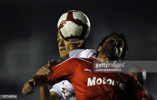 Argentina's Independiente midfielder Hernan Fredes vies for the ball with Ecuador's Liga Deportiva Universitaria defender Norberto Araujo during...