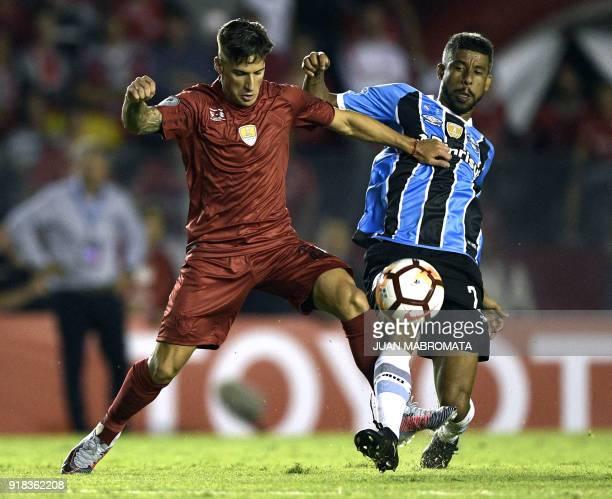 Argentina's Independiente midfielder Jonathan Menendez vies for the ball with Brazil's Gremio defender Leonardo Moura during their Recopa...