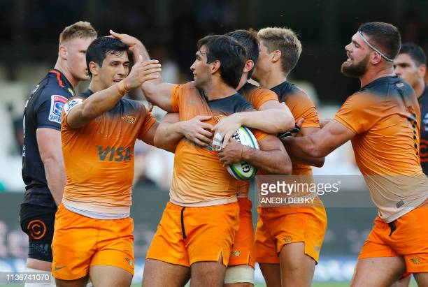 Argentina's Jaguares centre Matias Orlando celebrates with teammates including scrumhalf Tomas Cubelli after scoring a try during the Super Rugby...