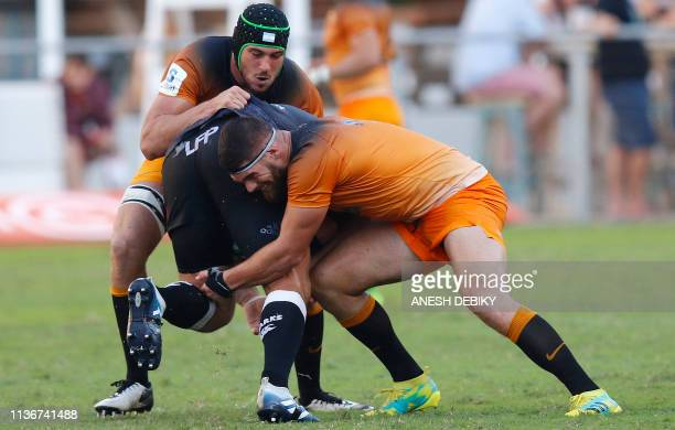 Argentina's Jaguares flanker Marcos Kremer and lock Guido Petti tackle a Sharks player during the Super Rugby match between Sharks and Jaguares at...