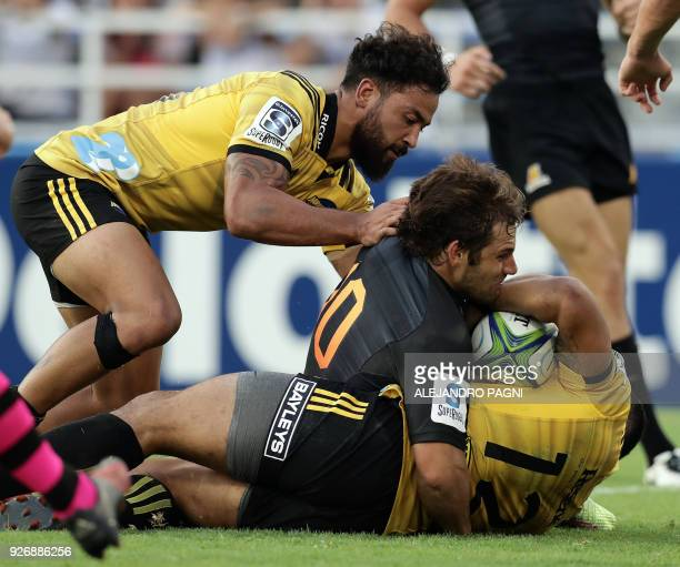 Argentina's Jaguares fly half Nicolas Sanchez vies for the ball with New Zealand's Hurricanes centre Matt Proctor and centre Ngani Laumape during...