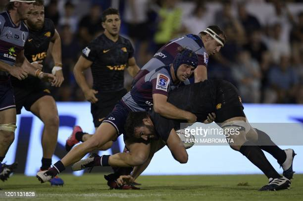 Argentina's Jaguares lock Lucas Paulos is tackled by Australia's Reds centre Hamish Stewart and prop JP Smith during the Super Rugby match at Jose...
