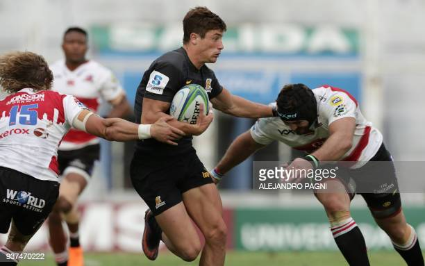 Argentina's Jaguares wing Bautista Delguy eludes South Africa's Lions fullback Malcolm Marx and flanker Lourens Erasmus during their Super Rugby...