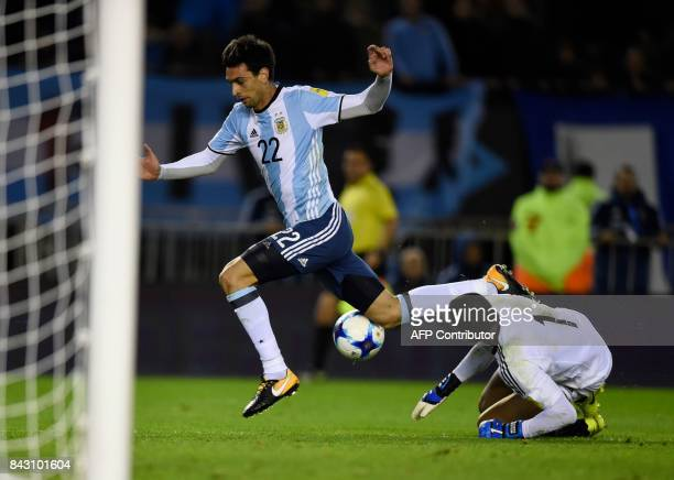 Argentina's Javier Pastore leaps over Venezuela's goalkeeper Wuilker Farinez during their 2018 World Cup qualifier football match in Buenos Aires on...