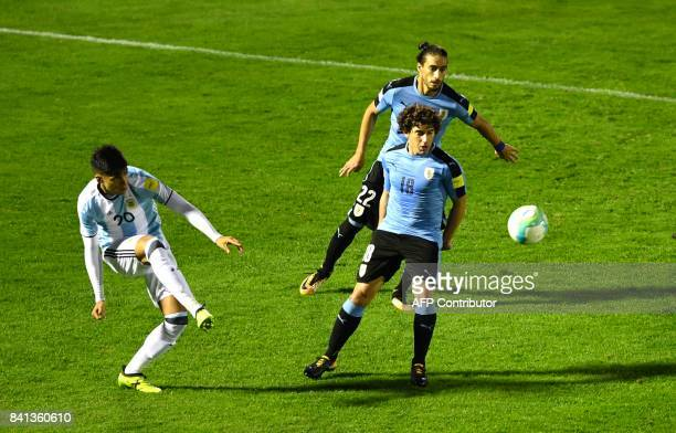 Argentina's Joaquin Correa strikes the ball next to Uruguay's Mathias Corujo and Martin Caceres during their 2018 World Cup qualifier football match...