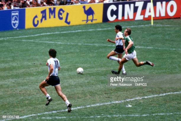 Argentina's Jorge Burruchaga outpaces West Germany's HansPeter Briegel to score the winning goal with teammate Jorge Valdano in support