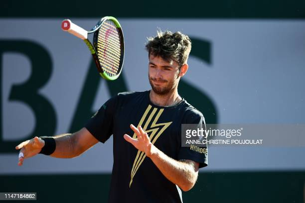 Argentina's Juan Ignacio Londero throws his racquet as he elebrates after winning against France's Corentin Moutet at the end of their men's singles...